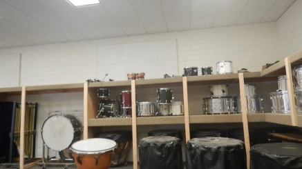 Percussion instruments neatly stored in newly renovated shelving.